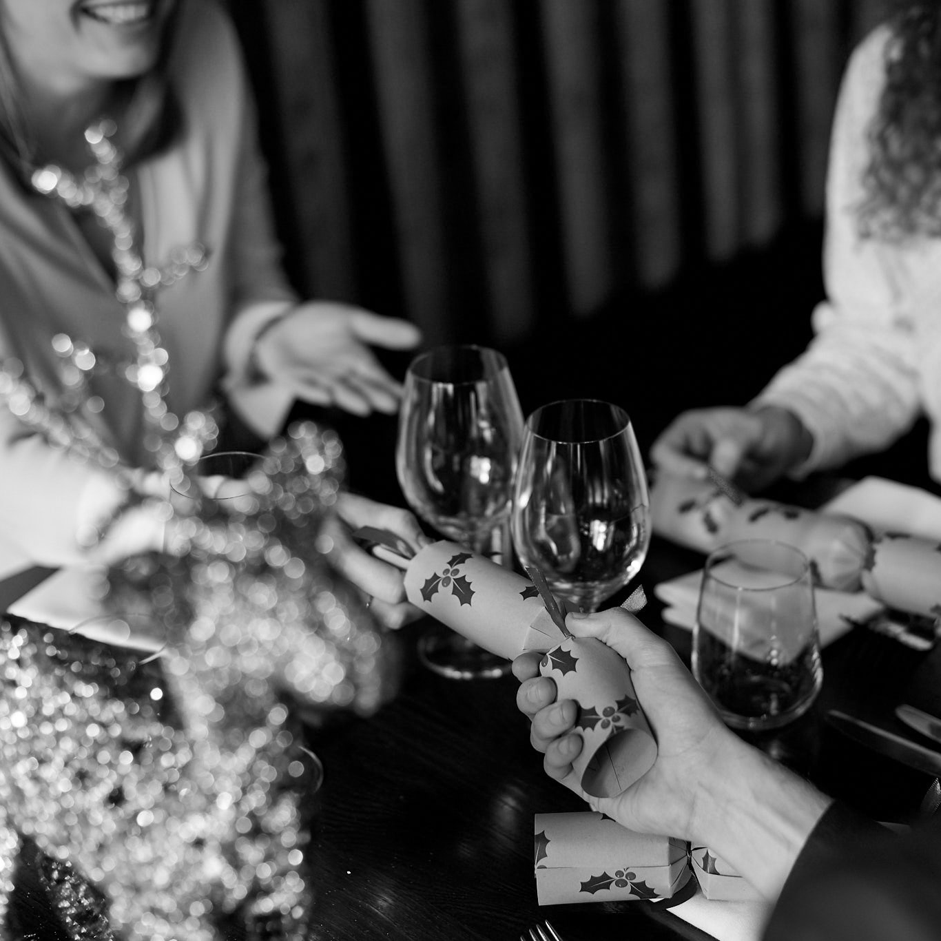 black and white image showing people at a table in Bistro Lago pulling a Christmas Cracker at a Christmas Day event